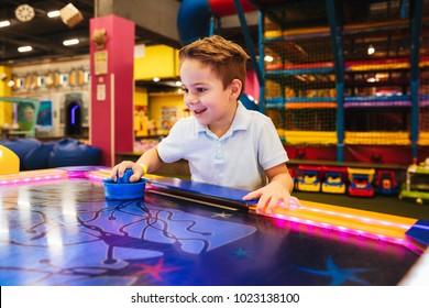 Cheerful little boy playing air hockey at Arcade centre