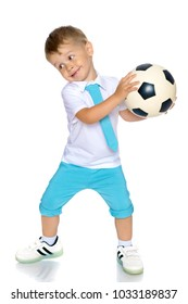 A cheerful little boy is playing with a ball in the studio on a white background. The concept of a happy childhood, game and sport. Isolated.