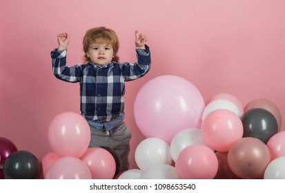 Cheerful little boy is playing with balls. Exciting games in kindergarten or children's center. The boy raised his hands and jumped. Active child. Games for children's development