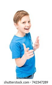 cheerful little boy pointing with fingers and smiling at camera isolated on white