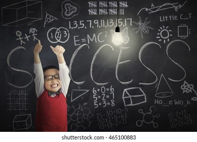Cheerful little boy showing OK sign with bright lightbulb and doodles on the blackboard, shot in the classroom