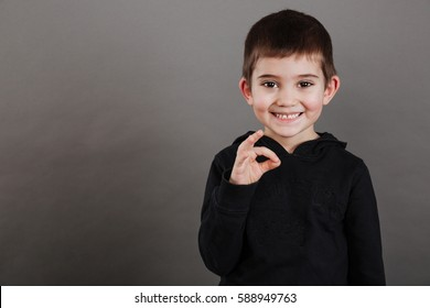 Cheerful little boy standing and showing ok gesture
