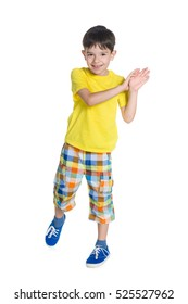 A cheerful little boy stands on the white background