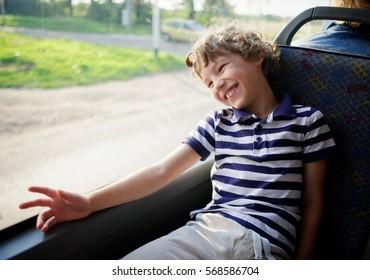 Der fröhliche kleine Junge in einem gestreiften T-Shirt fährt mit dem Bus. Sie sitzt an einem Fenster und lacht.