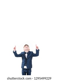 Cheerful little boy in suit looking and pointing up with both hands over white background with space for text