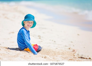 cheerful little boy in sunhat and rashguard playing in the sand at tropical beach, sun protection concept