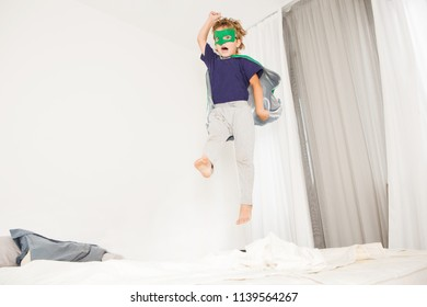 Cheerful little boy in Superhero costume  jumping on bed at home