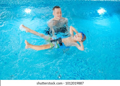 Cheerful little boy wearing swimming belt and goggles lying on back while his handsome coach teaching him to swim