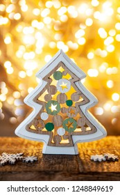 Cheerful little Christmas tree in front of bokeh lights