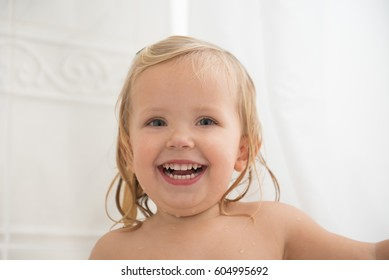 Cheerful little girl in bathroom looking at the camera. Beautiful wide smile of little girl with great healthy white teeth