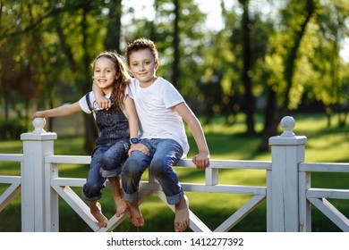 Cheerful little girl and boy sits on fence and hugs. Brother and sister in wet clothes in the summer park. Best friends. Childhood concept.