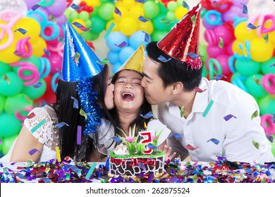 Cheerful little girl celebrate her birthday party with her parents and get kiss