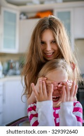 Cheerful little girl closes eyes to her sister.