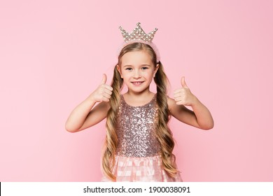 cheerful little girl in dress and crown showing thumbs up isolated on pink