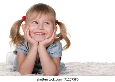 A cheerful little girl with funny tails is lying on the white carpet; isolated on the white background