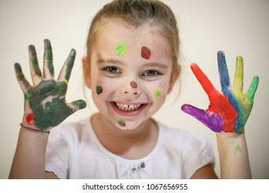 Cheerful Little girl with hands and face covered with paint. Space for copy.