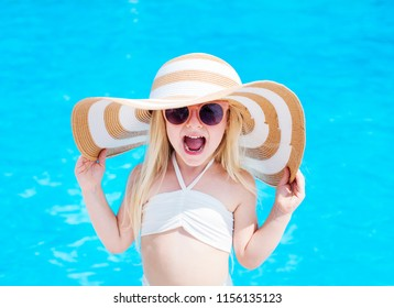 Cheerful little girl  with hat  next to swimming pool