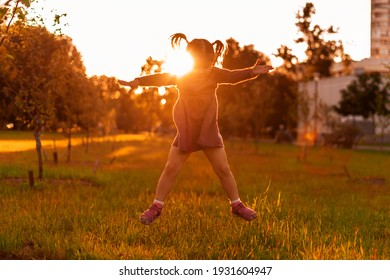 cheerful little girl having fun and jumping at sunset in the evening, flare, sun rays