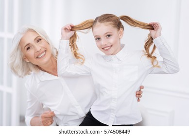 Cheerful little girl having fun with her grandmother