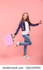 Cheerful little girl isolated over pink background, carrying shopping bags, walking