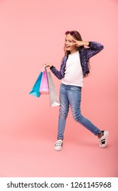 Cheerful little girl isolated over pink background, carrying shopping bags