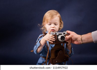 Cheerful little girl learning to do photos with the retro film camera and her dad helps her.