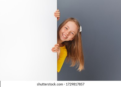 A cheerful little girl looks over a white wall or signboard highlighted on a white background.