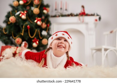 Cheerful little girl in a New Year's dress, posing on a background of the Christmas tree