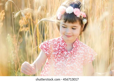 Cheerful little girl on the wheat field.