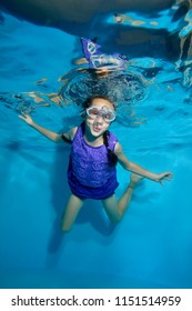 Cheerful little girl with pigtails swims underwater in the pool and lets bubbles. She looks at the camera and smiles in her swimming glasses and purple dress. Portrait. Vertical view.