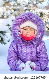 Cheerful little girl playing in a snowy forest