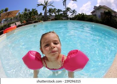 Cheerful little girl playing in swimming-pool