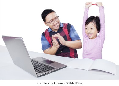 Cheerful little girl raising hands with her dad giving applause after finishing her study with laptop, isolated on white