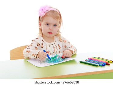 Cheerful little girl with short blond hair who is holding a pink headband in a bright silk shirt sitting at the table and drawing on a white sheet of blue felt-tip pen, lie near a lot of colored
