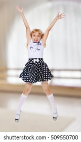 Cheerful little girl short skirt polka dot jumps with her arms and legs.In a room with a large semi-circular window.