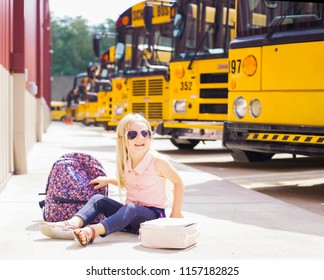 Cheerful little girl  sitting next to school buses. Backback, lunchbox and books next to her. Back to school concept.