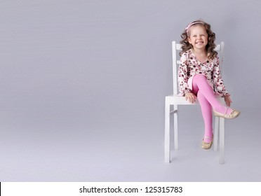 Cheerful little girl sitting on the chair with smile, a lot of copy space