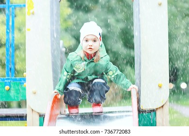 cheerful little girl walks and jumps in puddles in the rain