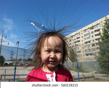 Cheerful little girl whose hair is like the sun on a background of blue sky.