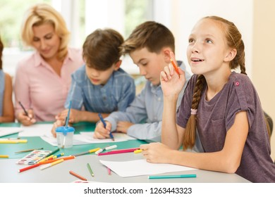 Cheerful little girl with woven two pigtails, sitting dreamily at school desk next to classmate. Female child leaning head to hand and smiling, looking up, holding few colored pencil in her hand near.