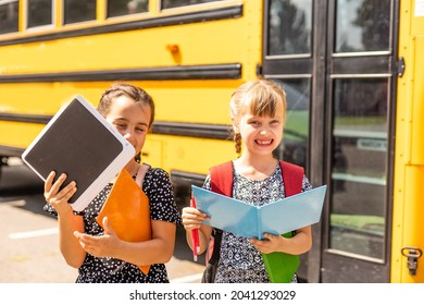 Cheerful little girls next to school bus. Backback. Back to school concept.