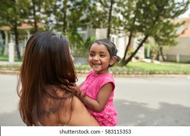 Cheerful little Indian girl looking away with toothy smile while having fun with her mother in front of their house