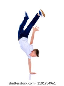 A cheerful little school-age boy is dancing breakdance. Isolated on white background.