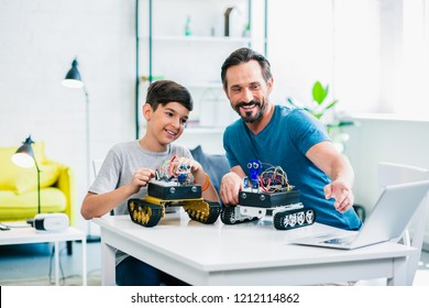 Cheerful little son and his father sitting at the table and testing their robots at home
