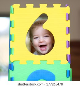 Cheerful little toddler girl playing hide and seek with colorful numbers puzzles