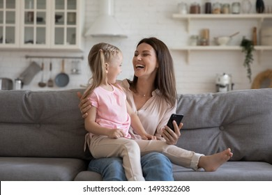 Cheerful lively daughter seated on mom lap enjoy online education programs, woman and her preschool charming kid girl spend free time together feels overjoyed use smartphone funny applications concept