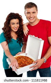 Cheerful love couple enjoying pizza together isolated against white background