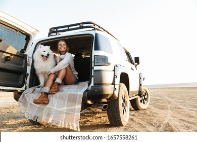 Cheerful lovely girl playing with her dog while sitting in a car at the beach