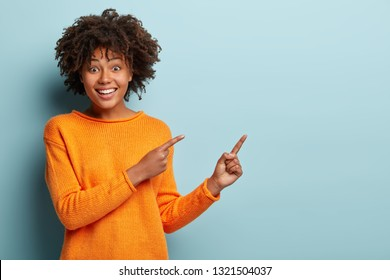 Cheerful lovely young girlfriend with broad smile, shows white teeth, indicates with both fore fingers at blank space, wears orange jumper, isolated over blue wall. Buy this thing on discount or sale