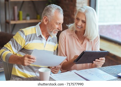 Cheerful loving aged couple involved in paperwork at home